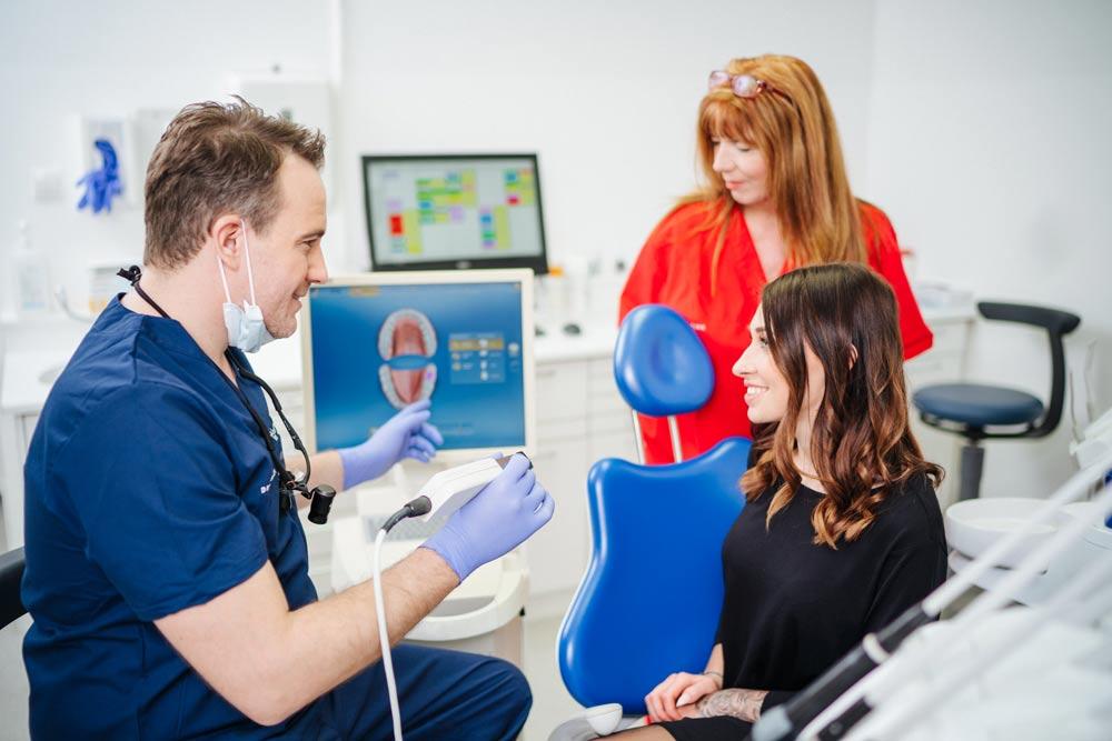 Dr. Berzaczy erklärt Patientin über Inlay Cad-Am auf, Frau Christine it im Hintergrund
