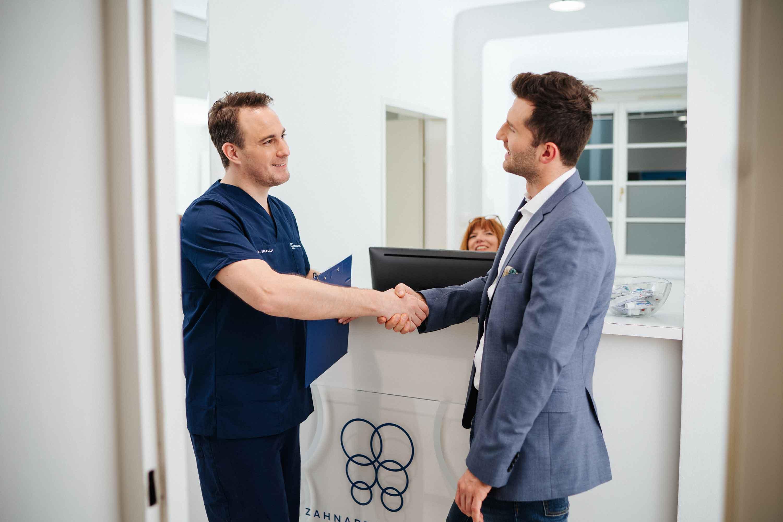 Dr. Berzaczy begrüßt Patient beim Empfang